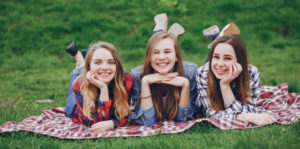 Three beautiful girls sitting in a park on a blanket